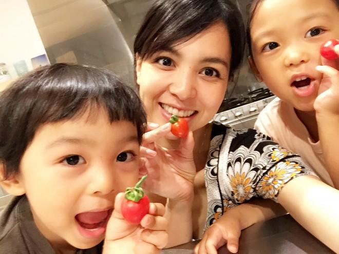 家庭菜園で採れたプチトマトを持った鈴木サチさんと子どもたち