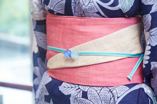 鮮やかなサーモンピンクの帯は、水色の帯締とガラス玉の帯留で涼しげに。