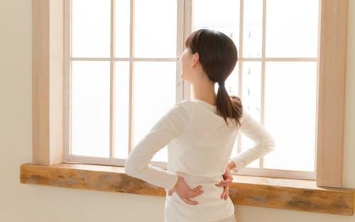 窓辺で腰に手をあてて外を眺める女性