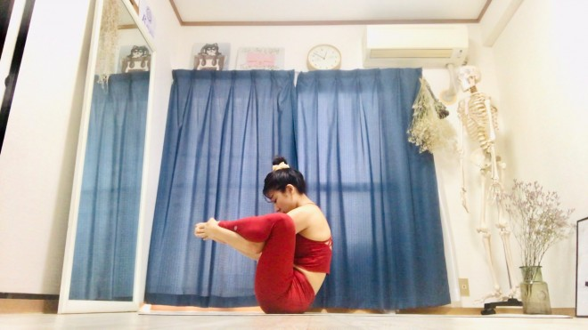 [1]坐骨と尾骨の3点でバランスをとりながら座り、脚を上げて膝を90°に曲げる。脚を開き、膝の下から腕をくぐらせ足の甲をそれぞれの手のひらで包む。顎を引いて臍を見、背中はCカーブをキープする。