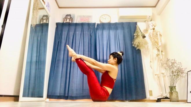 [1]脚を上げ、尾骨と鎖骨の3点でバランスをとって座る。足首を真上から手のひらでつかむ。背骨を長く伸ばし、片脚ずつ膝を伸ばして脚を開く。